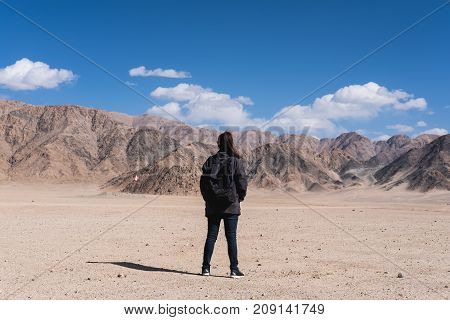 Portrait image of a beautiful Asian woman tourist standing and turn back in front of mountain and blue sky background