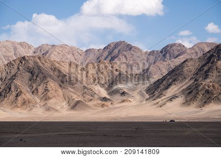 Landscape image of mountains and blue sky background with people and cars in Leh Ladakh India