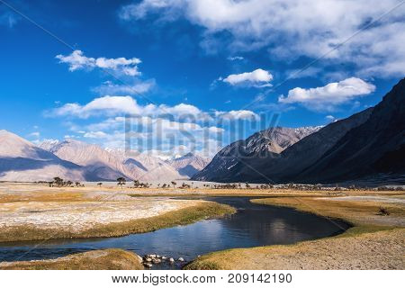 Landscape image of desert stream and mountains with blue sky background