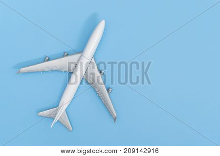 Plastic toy plane on blue copy space background for travel concept