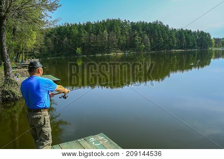 Fisherman on the river bank throws a fishing pole