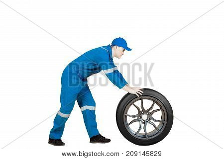 Side view of American male mechanic pushing a car wheel in the studio isolated on white background