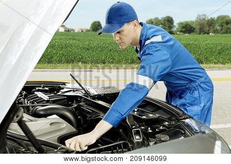 Image of an American male mechanic checking broken car machine with a laptop while standing on the roadside
