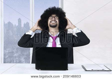 Afro businessman has trouble and his hands on head while working with a laptop and clipboard on the desk