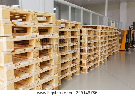 few empty wooden pallets for storage in an empty warehouse. soft focus and bokeh.