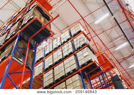 Warehouse address storage of goods and materials on shelves in large cardboard boxes. View from the bottom up.