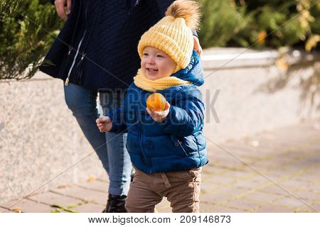 happy little boy in the rays of the sun in autumn, in the leaves and a yellow cute cap holding clementine