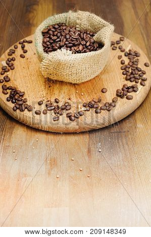 Coffee beans and sack bag on old wooden background, copy space for text, vintage style