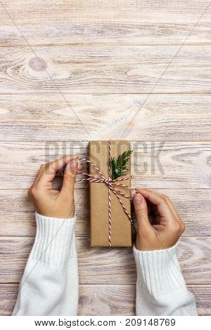 Women binds classic bow for gift. Hands of woman decorating Christmas gift box.