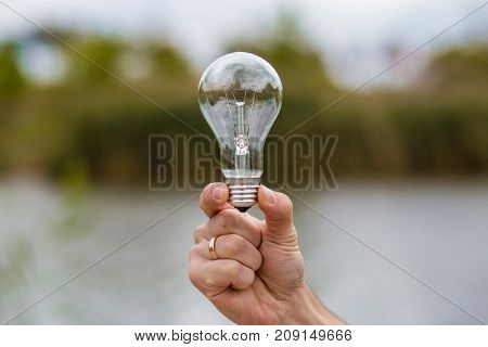 Men's Hand holding Light Bulb Electric on nature background, idea concept