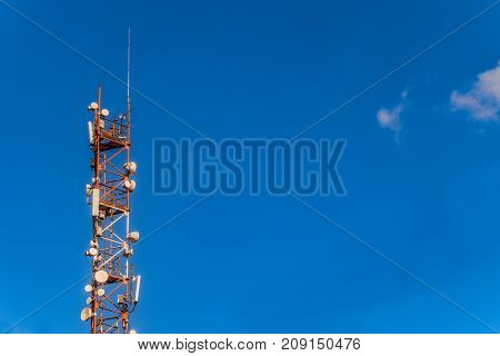 Mast of radio communication equipment on a blue sky background