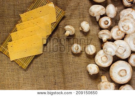 Ingredients. thin slices of yellow cheese and raw champignons on burlap. View from above