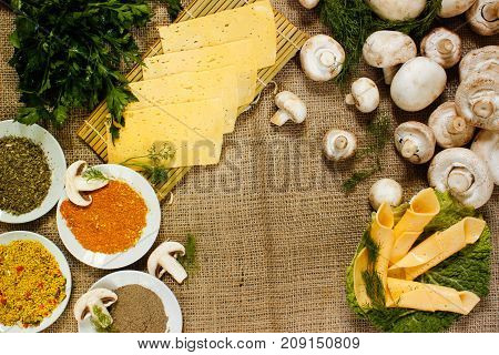 Ingredients. spice parsley thin slices of yellow cheese on a green salad sheet and raw champignons on burlap. View from above
