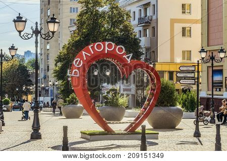 Belgorod Russia - September 29 2017: Street of the fiftieth anniversary of the Belgorod region. Pedestrian street in the old residential center of the city. Urban environment. Bench of love in the shape of a heart with flower pots.