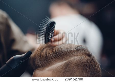 Barbershop. Close-up of a man's haircut, the master does the hair styling