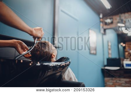Close-up: a hairdresser washes a client's head for a man