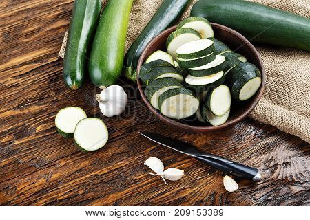 zucchini sliced and whole zucchini lying on the board. Space for text