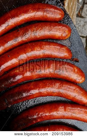 Paprika Bratwurst Sausages On Cast Iron Griddle From Above.