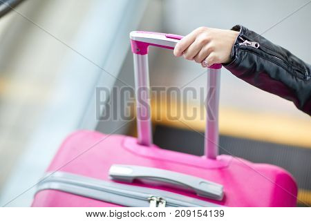 Pink suitcase close-up with hand to girl in leather jacket on handle on blurred background