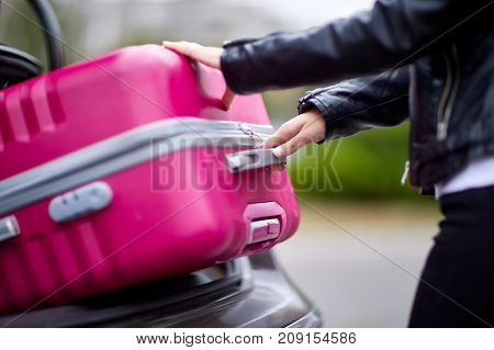 A beautiful girl in a leather jacket picks up a suitcase to put in the trunk of a black car