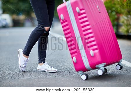 A young, pretty girl with a pink suitcase standing on the street legs and a suitcase close-up