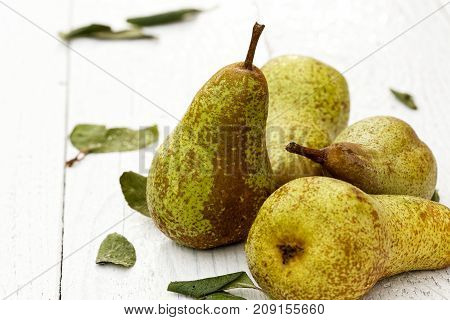 Four abate fetel pears with leaves on white painted wood. poster