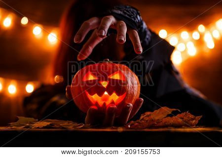 Image of witch with long hairs holding pumpkin on background with burning garlands