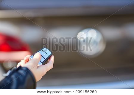 Hand of a girl close-up in a leather jacket with a remote control from her car