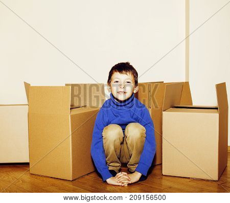 little cute boy in empty room, move to new house. home alone among boxes close up kid smiling, lifestyle real people concept closeup