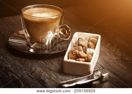 cup of coffee in coffee shop vintage color. Coffee grinder and Brown cane sugar on wooden table with flare blurred background. Retro style image. Glare of light.