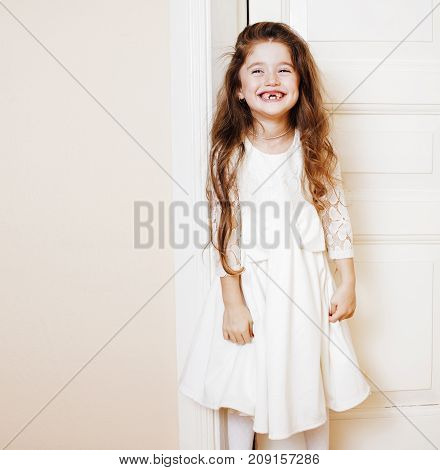 little cute girl at home, opening door well-dressed in white dress and tiara, adorable milk fairy teeth copyspace