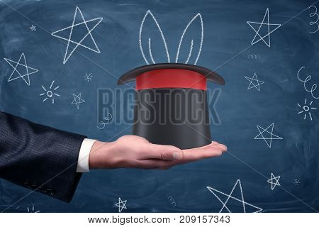 A businessman's palm with a magician's hat resting on it and drawings of stars and rabbit ears around. Business tricks. Thinking out of box. Creativity and innovation.