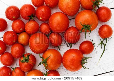 Many Wet Red  Tomatoes With Stalks On White Wood Board From Above.