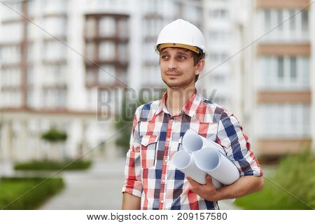 Young male architect with blueprints posing outdoors in front of a building looking away professionalism occupation career achievement inspiration experience concept