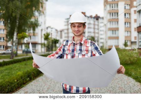 Professional builder architect examining architectual blueprint standing outdoors. Young engineer in a hardhat inspecting architectual sketch outdoors project management experience concept
