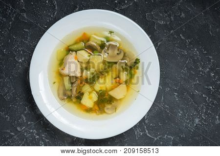 Soup with Mushrooms and chicken on stone background top view