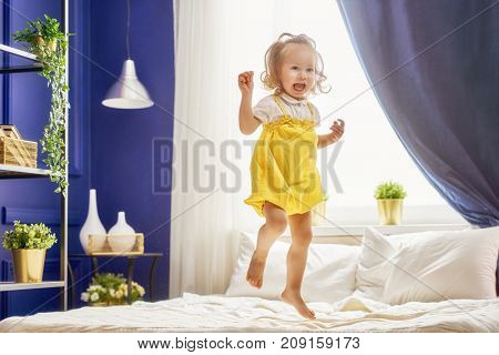 Beautiful smiling cute baby girl in the room at home. Happy child laughing and jumping on the bed.