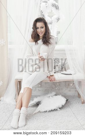 Attractive young woman resting at home, drinking tea. All white.