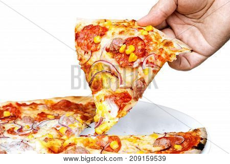 Man's Hand Holding A Slice Of Salami And Sweetcorn Pizza. White Background.