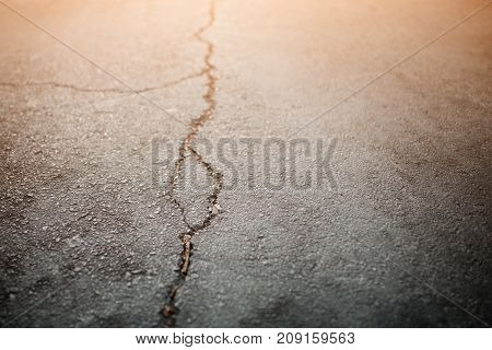 Texture of the old road with cracks. Asphalt surface on the street. Glare of light.