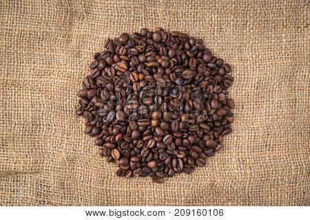Pile of coffee beans in the middle on jute background.