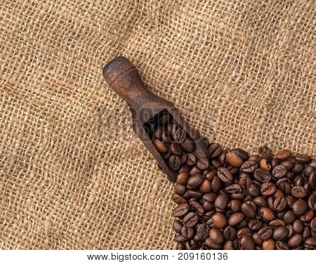 Scooper with coffee beans on jute background.