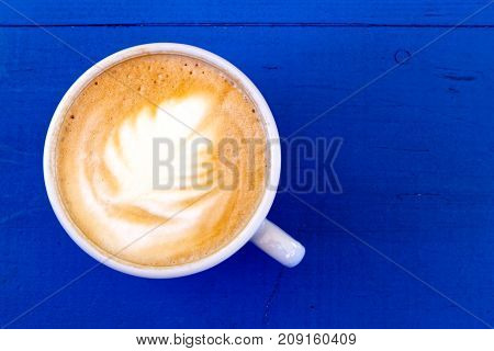 Cappuccino In White Ceramic Cup On Blue Painted Wood From Above.
