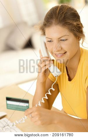 Credit card shopping. Happy young woman sitting in living room at home, talking on phone, shopping with credit card, smiling.