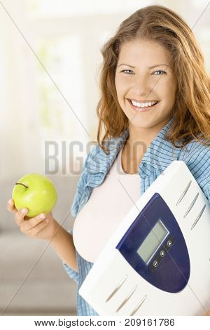Happy young woman holding bathroom scale and apple, looking at camera, smiling.