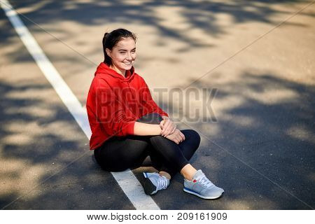 Sporty girl sits on the ground on a sunny autumn day