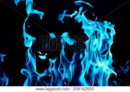 Blue flames on a black background . Photo of abstract background
