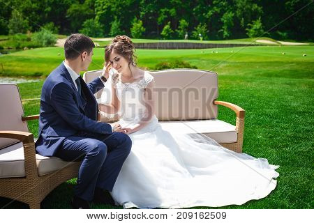 portrait of newlywed couple sitting on white sofa. Bride in beautiful white wedding dress and asian groom in dark blue suit. tender and love