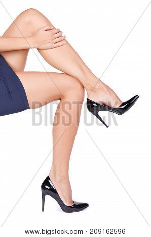 A black lacquered high heel shoes on female's foot isolated on a white background. Close-up of hills. Fashion concept.