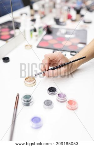 The hand of the make-up artist keeps the brush. Colored circles of confetti for design isolated on white background. Close-up. View from above.